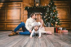 Family holiday New Year and Christmas. Young caucasian family mom dad son 1 year sit wooden floor near fireplace christmas tree on royalty free stock photography