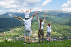 Family holiday. Parents and children stand with their hands up. Mountains on the background. Back view stock image