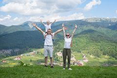 Family holiday. Parents with a small son stand with their hands. Up. Mountains on the background Stock Images