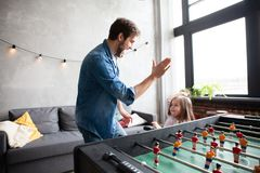 Father and daughter playing table football at home. Family holiday and togetherness. Father and daughter playing table football at home royalty free stock photography