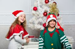 Family holiday tradition. Children cheerful celebrate christmas. Siblings ready celebrate christmas or meet new year. Kids christmas costumes santa and elf stock photography