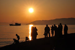 Family holidays. Big family watching sunset at the seaside Royalty Free Stock Photo