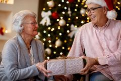 Family, holidays, age and people concept - smiling senior couple. Family, holidays, age and people concept - lovely smiling senior couple with Christmas gift Royalty Free Stock Image