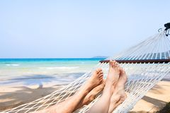Family holidays on the beach, feet of couple in hammock, relaxation. Background royalty free stock photo