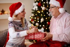 Family, holidays, Christmas, age and people - daughter and elder. Family, holidays, Christmas, age and people concept - daughter and elderly father sharing Royalty Free Stock Photo