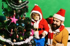 Family holidays concept. Boy and man with beard. And happy faces put Christmas ball on tree. Christmas family decorates fir tree on green background. Santa and royalty free stock photos