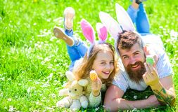 Family holidays concept. Child and man with cute bunny ears play together. Girl with dad lying on grass on sunny day royalty free stock photo