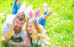 Family holidays concept. Child and man with cute bunny ears play together. Girl with dad lying on grass on sunny day stock photos
