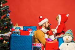 Family holidays concept. Man with beard and smiling face. Plays with son. Christmas family opens presents on dark red background. Santa and little assistant royalty free stock image