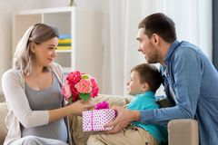 Family giving present to pregnant mother at home. Family, holidays and greetings concept - father and little son giving flowers and present to happy pregnant Stock Image