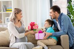 Family giving present to pregnant mother at home. Family, holidays and greetings concept - father and little son giving flowers and present to happy pregnant Stock Images