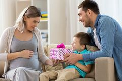 Family giving present to pregnant mother at home. Family, holidays and greetings concept - father and little son giving present to happy pregnant mother at home Royalty Free Stock Images