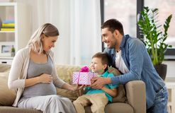Family giving present to pregnant mother at home. Family, holidays and greetings concept - father and little son giving present to happy pregnant mother at home Stock Photos