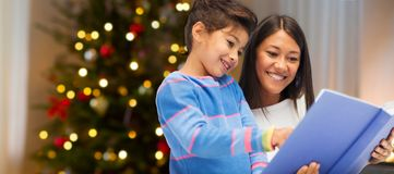 Mother and daughter reading book on christmas. Family, holidays and people concept - happy mother and daughter reading book over christmas thee lights background stock images