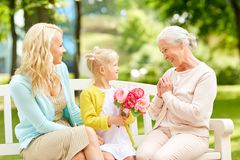 Happy family giving flowers to grandmother at park Royalty Free Stock Photos