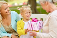 Happy family giving present to grandmother at park Stock Photography