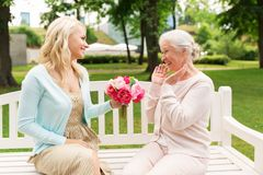Daughter giving flowers to senior mother at park Stock Photos