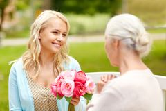 Daughter giving flowers to senior mother at park Stock Photo