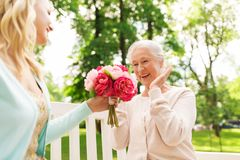 Daughter giving flowers to senior mother at park Stock Image