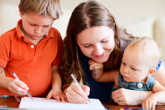Family at home. Young mother and her two kids drawing together. Can be used also in kindergarten/daycare context stock image
