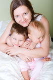 Family at home. Happy young mother with her son and daughter in bedroom royalty free stock photos
