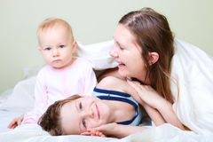 Family at home. Beautiful young mother with two kids in bedroom. Focus on boy royalty free stock images