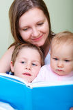 Family at home. Young mother with her two kids reading book in bed royalty free stock image