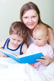 Family at home. Young mother with her two kids reading book in bed stock photos