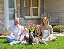 Family at Home. Family Sitting in Front of Their Home Royalty Free Stock Photography