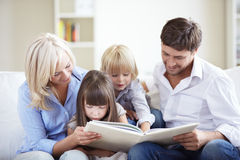 Family at home. Family reading a book at home on the couch Stock Images
