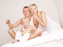 Family at home. Happy family; mother ,father and their son watching TV and eating popcorn in  bed at home Royalty Free Stock Image