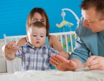 Family at home. Portrait of happy family at home. Baby boy ( 1 year old ) and young parents father and mother sitting on floor and playing together at children's stock photography