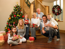 Family at home around christmas tree. Exchanging gifts Stock Photography