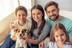 Family at home. Beautiful young parents, their cute little daughter and son are looking at camera and smiling, sitting with their cute dog on sofa at home Stock Photo