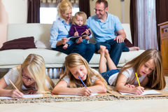 Family at home, the children coloring on floor Royalty Free Stock Photography