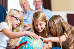 Family at home, the children playing with a globe royalty free stock photography