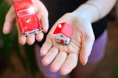 Family home concept. Miniature house and car in female hands. royalty free stock image