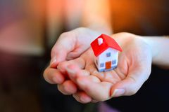 Family home concept. Miniature house in female hands. Buying your own home concept. Family home concept. Miniature house in female hands stock photography