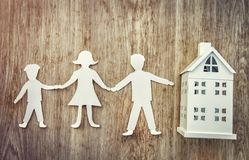 Family and home concept. Paper father, mother and son holding hands near miniature house on wooden background. Stock Photos