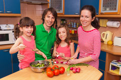 Family at home cooking salad Stock Photography