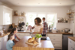 Family At Home Eating Breakfast In Kitchen Together stock photo