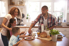 Family At Home Eating Breakfast In Kitchen Together stock image