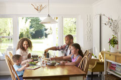Family At Home Eating Meal In Kitchen Together royalty free stock image