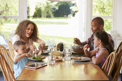 Family At Home Eating Meal In Kitchen Together royalty free stock photography