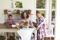 Family At Home Eating Outdoor Meal Together stock photos