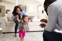 Family At Home Encouraging Baby Daughter To Take First Steps royalty free stock image