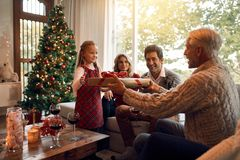 Family at home exchanging christmas presents. Grandfather giving gift to little girl for christmas and new year. Family sitting in living room exchanging Stock Photos