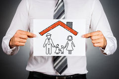 Family and home insurance concept. Businessman holding white paper with drawing of a family, under the home roof royalty free stock image