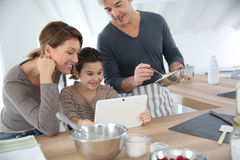 Family at home kitchen cooking together with tablet Royalty Free Stock Photos