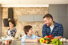 Family at home in kitchen together father and son standing looking at each other cheerful while mother answering call on stock images